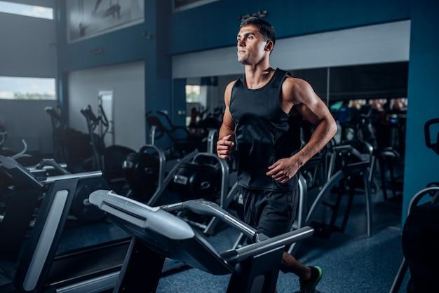 Männliches athletentraining auf laufendem übungsgerät. aktives sporttraining im fitnessstudio