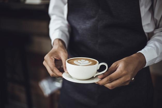 Männliches barista, das kaffee für kunden in der kaffeestube zubereitet. caféinhaber, der einen kunden an der kaffeestube dient.