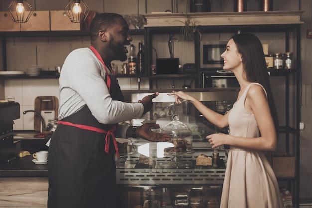 Männliches barista hilft einem mädchen, einen nachtisch zu wählen