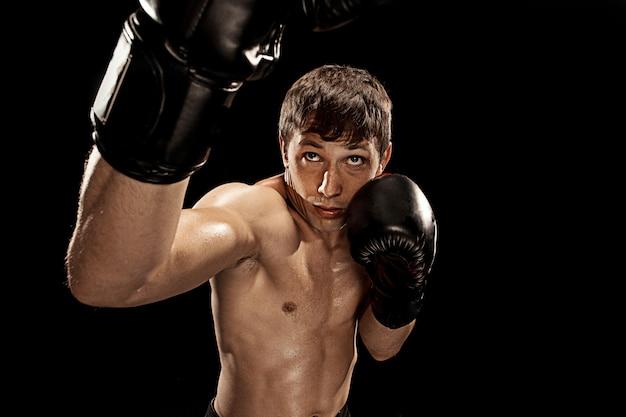 Männliches boxerboxen im sandsack mit drastischer nervöser beleuchtung