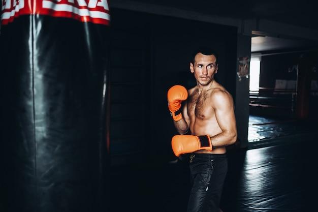Männliches boxertraining mit sandsack in der dunklen turnhalle.