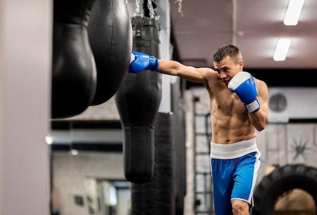 Männliches boxertraining mit schutzhandschuhen