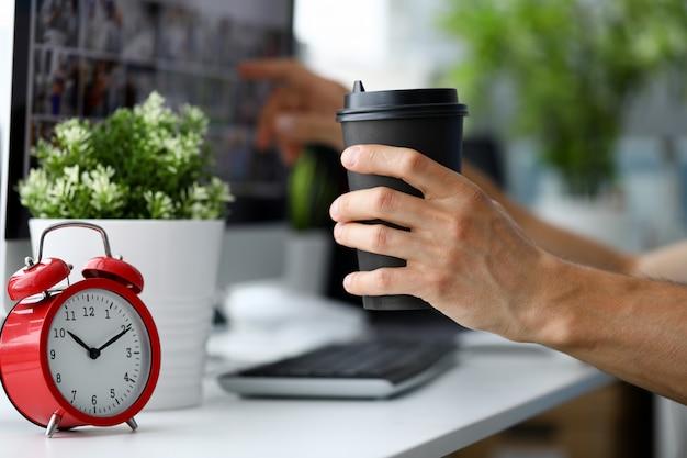 Männliches handgriffschwarzpapierkaffeetasse aganist büro
