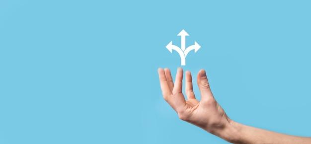 Männliches handhaltesymbol mit symbol für drei richtungen auf blauem oberflächenzweifel bezweifelt, zwischen drei verschiedenen auswahlmöglichkeiten wählen zu müssen, die durch pfeile angezeigt werden, die in drei richtungen in das konzept der entgegengesetzten richtung zeigen