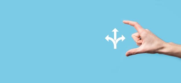 Männliches handhaltesymbol mit symbol für drei richtungen auf blauem oberflächenzweig zweifel, zwischen drei verschiedenen auswahlmöglichkeiten wählen zu müssen, die durch pfeile angezeigt werden, die in die entgegengesetzte richtung zeigen