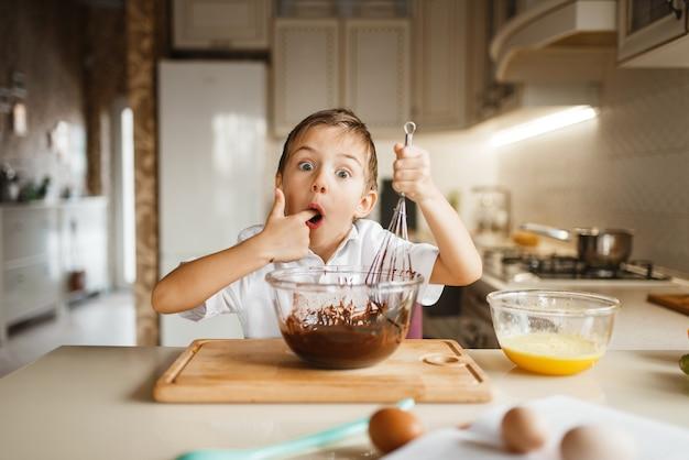 Männliches kind schmeckt geschmolzene schokolade in einer schüssel
