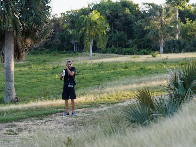 Männliches läufertrinkwasser aus plastikflasche nach cardio-training, tragend weiße kopfhörer. sportler in schwarzer sportbekleidung, die während des trainings im freien feuchtigkeit spendet.