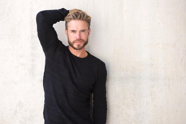 Männliches mode-modell, das mit der hand im haar aufwirft