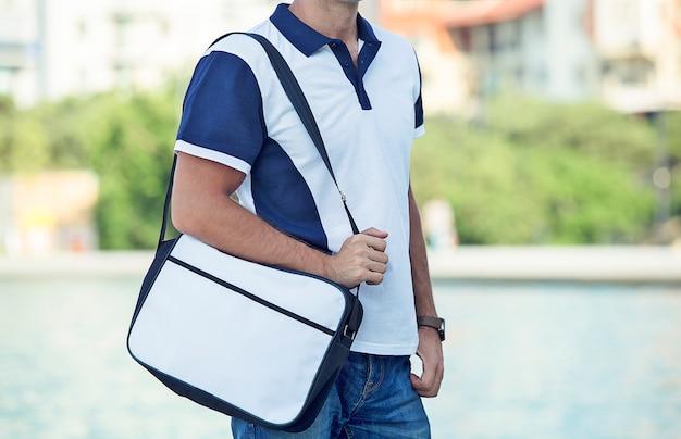 Männliches mode-modell, das zufälliges polo und paket fördert