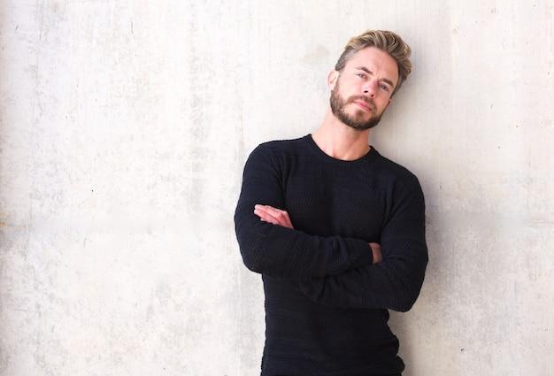 Männliches mode-modell mit dem bart, der mit den armen gekreuzt aufwirft