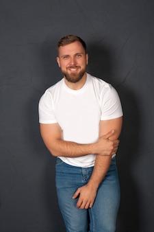 Männliches model mit einer aufgebauten figur in jeans und einem weißen t-shirt. das konzept von stilvollen männern, kleidung für männer, jeans, lässigem stil oder einer lebensweise.