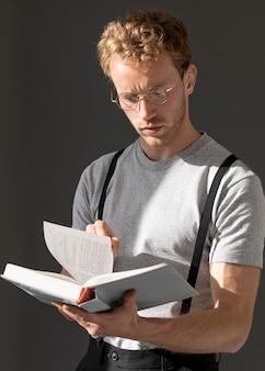 Männliches modell, das hosenträgerzubehör trägt und liest