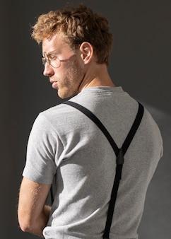 Männliches modell, das hosenträgerzubehör von hinten schuss trägt