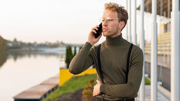 Männliches modell, das wegschaut und am telefon spricht
