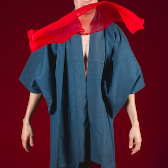 Männliches modell der vorderansicht, das mit rotem stoff aufwirft