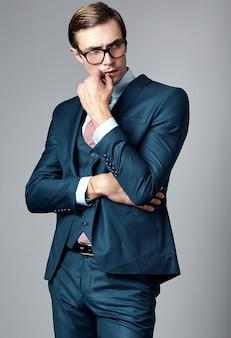Männliches modell des jungen eleganten hübschen geschäftsmannes in der blauen klage und in den modernen gläsern, werfend im studio auf