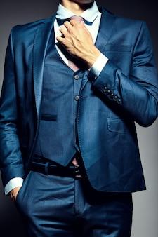 Männliches modell des jungen eleganten hübschen geschäftsmannes in einem anzug, der die krawatte bindet