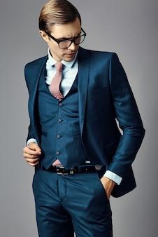 Männliches modell des jungen eleganten hübschen geschäftsmannes in einer klage und in modernen gläsern, werfend im studio auf