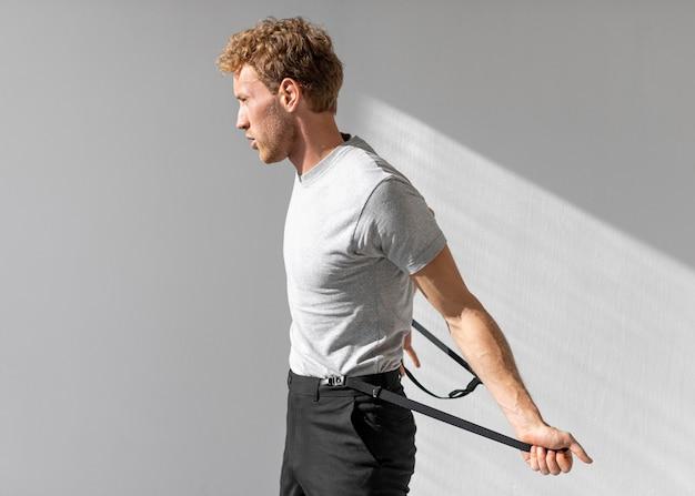 Männliches modell hält seine hosenträger