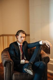 Männliches modell im schwarzen anzug und in der roten bindung wirft für die kleidungswerbung der männer auf. dreharbeiten für herrenbekleidungsgeschäft