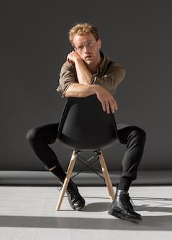 Männliches modell mit dem lockigen haar, das auf einem bürostuhl sitzt