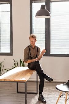 Männliches modell mit lockigem haar, das auf dem tisch lange einstellung sitzt