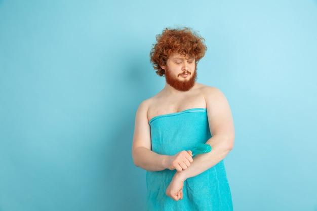 Männliches modell mit natürlichem rotem haar, das gesichtshaut mit spezieller walze massiert