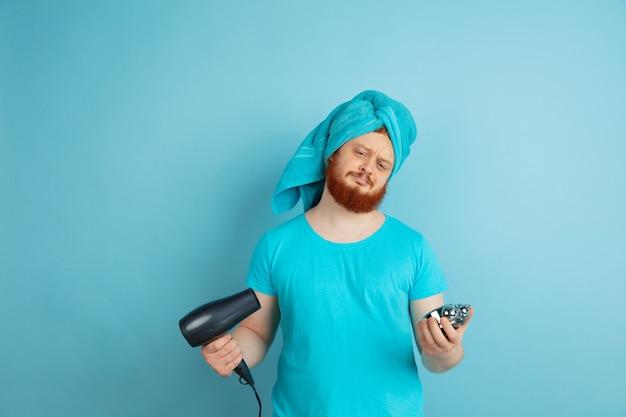 Männliches modell mit natürlichem rotem haar, das seinen bart trocken bläst und frisur bildet