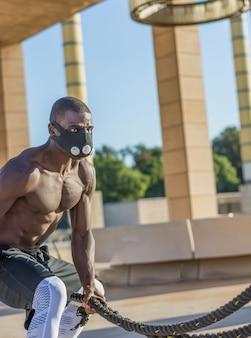 Männliches muskulöses training mit kampfseilen und trainingsmaske