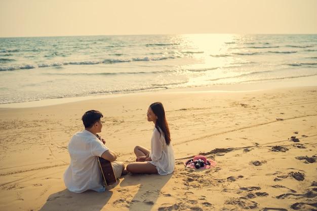 Männliches paar, welches die gitarre sitzt sitzend spielt. lebe am strand