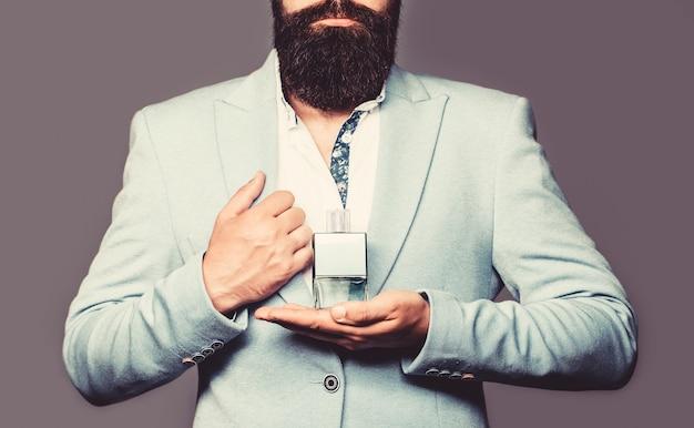 Männliches parfüm, bärtiger mann im anzug. mann, der eine flasche parfüm im anzug hält. bärtiger mann, der eine flasche parfüm hält. parfüm- oder kölnischwasserflasche und parfümerie, duftölflasche.