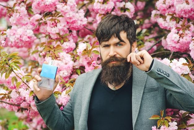 Männliches parfüm. frühlingsblumen. mann parfüm, duft. herrenduft und parfümerie, kosmetik. mann hält flasche parfümerie hoch.