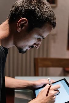 Männliches profil mit piercings unter verwendung einer tablette mit einem digitalen stift