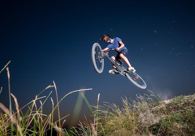 Männliches radfahrerfliegen auf einer mountainbike gegen abendhimmel in den bergen
