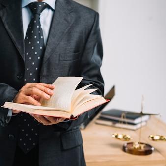 Männliches rechtsanwaltlesebuch, das vor schreibtisch steht