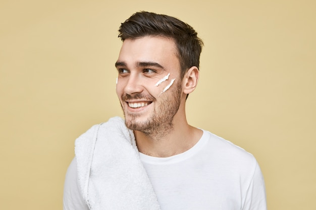 Männliches schönheitskonzept. glücklicher attraktiver junger kaukasischer mann mit der borste, die im badezimmer am morgen mit handtuch auf schulter aufwirft und mit lächeln wegschaut, nach rasiercreme auf seinem gesicht