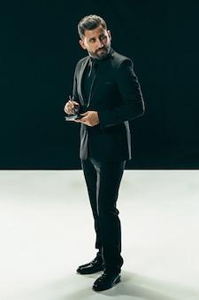 Männliches schönheitskonzept. porträt eines modischen jungen mannes mit stilvollem haarschnitt, der trendige anzugaufstellung trägt