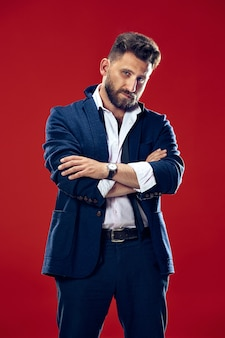 Männliches schönheitskonzept. porträt eines modischen jungen mannes mit stilvollem haarschnitt, der trendigen anzug trägt, der über rot aufwirft. perfektes haar