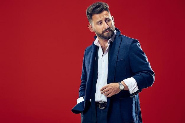 Männliches schönheitskonzept. porträt eines modischen jungen mannes mit stilvollem haarschnitt, der trendigen anzug trägt, der über rotem hintergrund aufwirft.