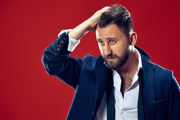 Männliches schönheitskonzept. porträt eines modischen jungen mannes mit stilvollem haarschnitt, der trendigen anzug trägt, der über roter wand aufwirft.
