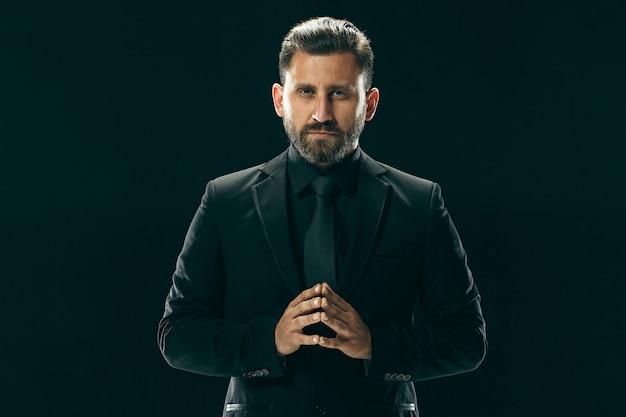 Männliches schönheitskonzept. porträt eines modischen jungen mannes mit stilvollem haarschnitt, der trendigen anzug trägt, der über schwarzem studiohintergrund aufwirft.