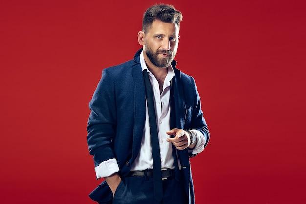 Männliches schönheitskonzeptporträt eines modischen jungen mannes mit stilvollem haarschnitt, der einen trendigen anzug trägt, der über roter wand posiert