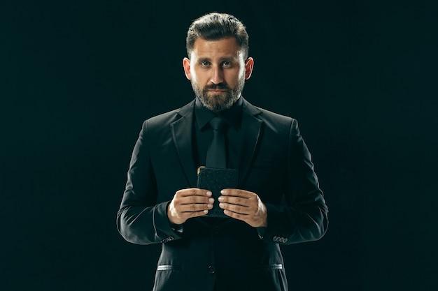 Männliches schönheitskonzeptporträt eines modischen jungen mannes mit stilvollem haarschnitt, der trendigen anzug trägt, der über schwarzer wand aufwirft