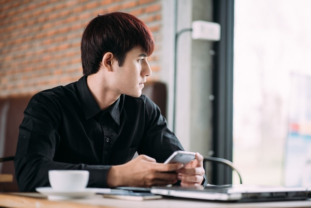 Männliches sitzen am tisch mit dem laptop und tasse kaffee, die durch ein fenster schauen