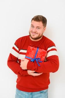 Männliches wintermodell, welches das geschenk hält