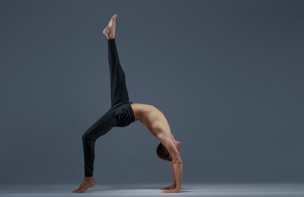 Männliches yoga, das streckübung auf grauem hintergrund tut. starker mann, der yogi, asana-training, höchste konzentration, gesunden lebensstil praktiziert
