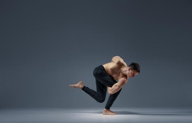 Männliches yoga hält das gleichgewicht in einer schwierigen pose, grauer hintergrund. starker mann, der yogiübung, asana-training, höchste konzentration, gesunden lebensstil tut
