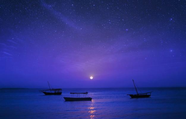 Märchenhafte nachtlandschaft afrika, tansania, sansibar. schattenbild von fischerbooten auf hintergrund des sternenhimmels im ozean