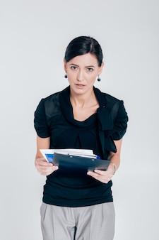 Märtyrer geschäftsfrau, die einen ordner mit dokumenten auf einem grauen hintergrund hält