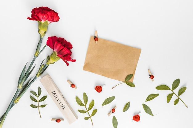 März-inschrift mit nelkenblumen und papier